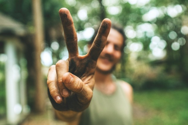 Man showing a victory sign with two dirty fingers. Apparently he's outdoors and happy. Greenery is around him.