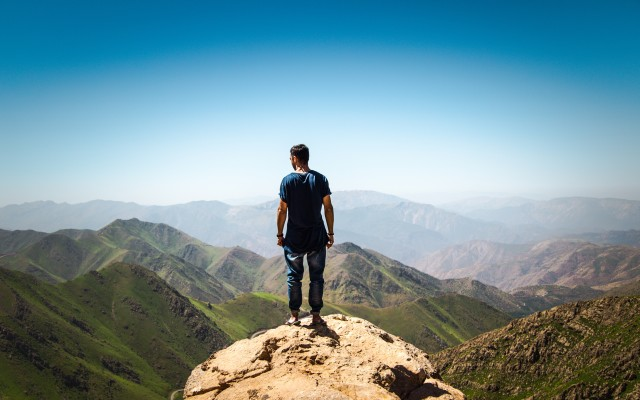 Green iranian mountains. A man stands on top of a rock and looks at them.