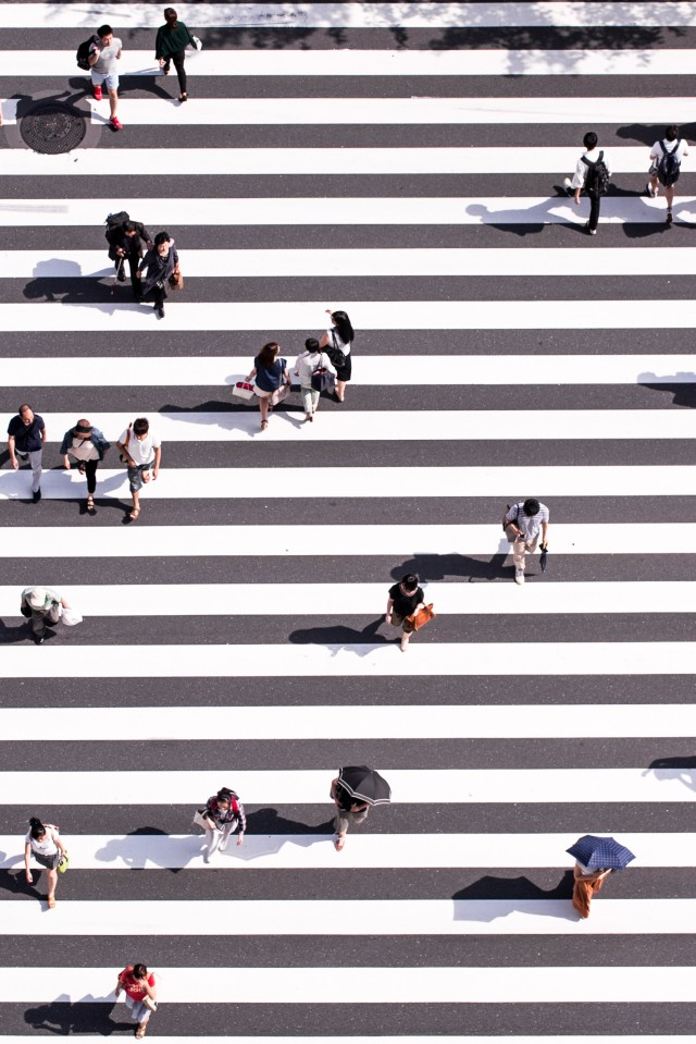 Bird view of people crossing a road on a busy intersection.