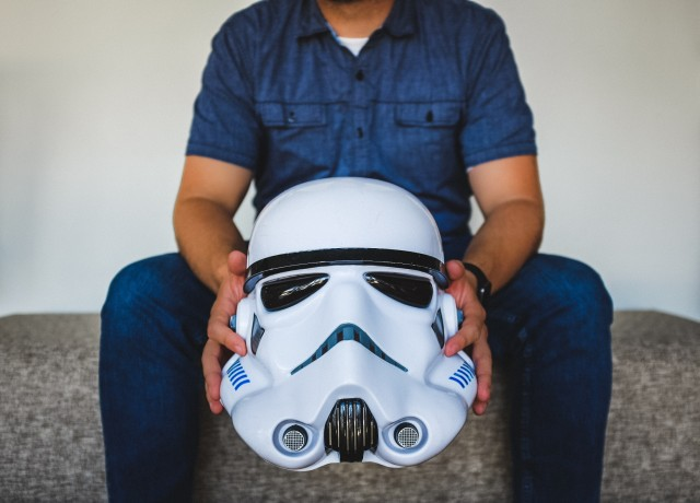 Man sitting outside - wearing casual jeans - holding a large Star Wars stormtrooper mask/helmet in front of him. You don't see his face though, it's above the picture.