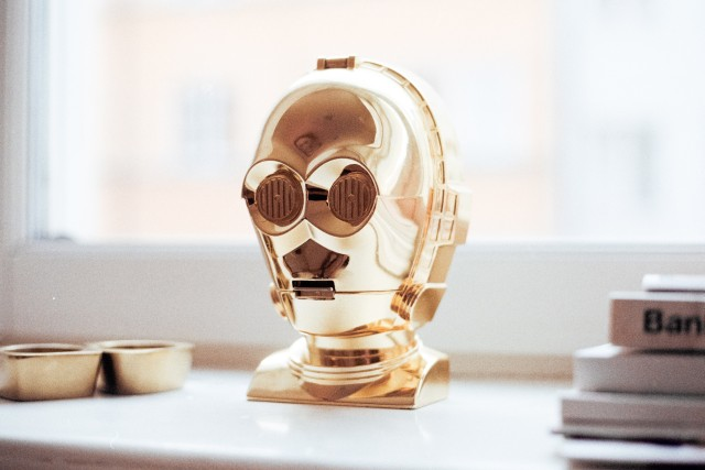 A golden robot head of C3Po from Star Wars stands on a window sill beside some books and stuff.