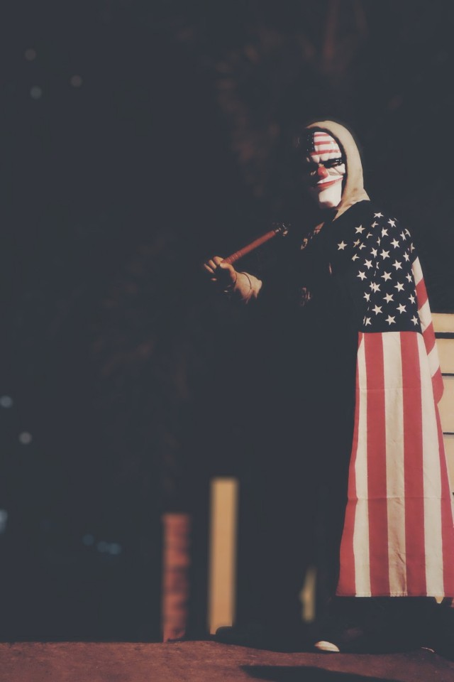 Creepy looking man wearing a mask and dressed in the American stars and stripes flag. He also holds a baseball bat.