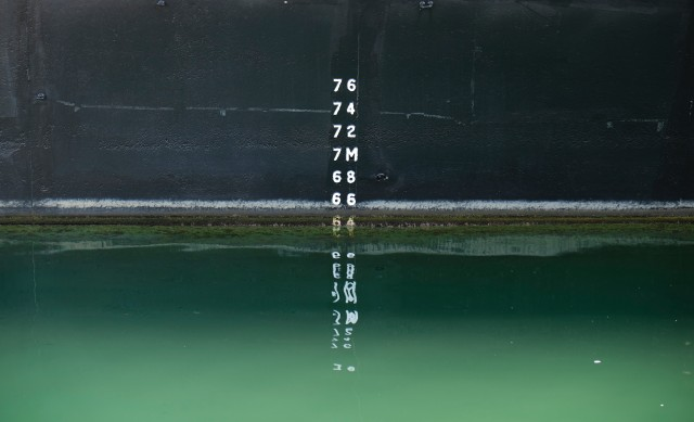 A teal body of water with a measuring scale up to 7.6 meters. It's a bit above 6m now and it's green.