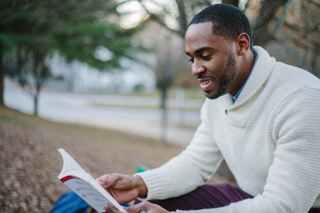 Very smypathetic looking brown skinned colored guy reading a book on a park bench.
