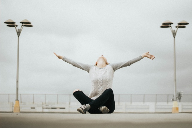 Woman sitting cross-legged on a bridge on a grey cloudy day yet she seem exhilarated and happy because she looks up in the sky and raises her arms.