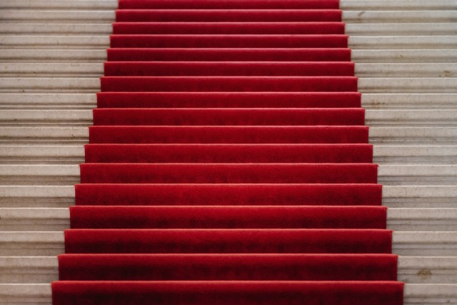 A red carpet covers broad stairs at a museum in Geneva, Switzerland. It looks inviting.
