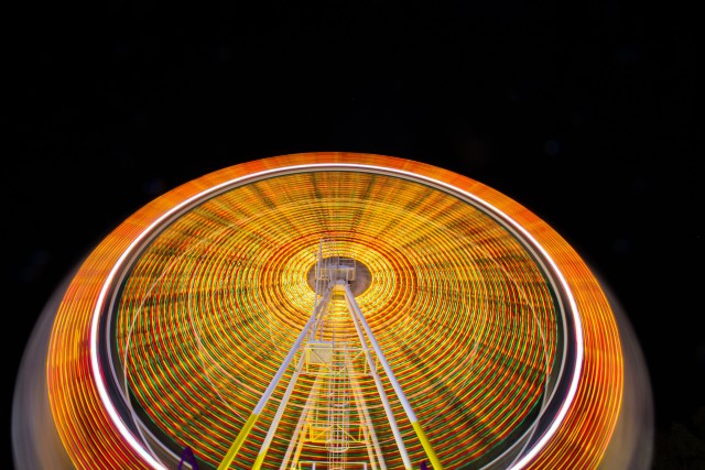 Orange merry-go-round spinning so fast you only see a light circle at night.