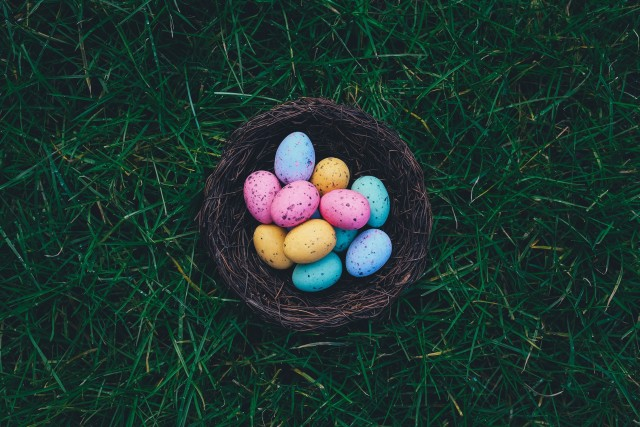 A self-made Easter basket with colorful eggs standing on the grass.