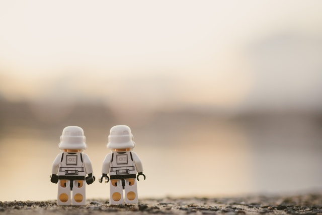 Two sztormtroopers standing side by side looking into the hazy distance of the desert.