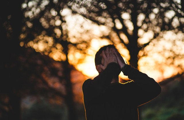 A man holds his hands over his face in front of trees at sunset. He may be hiding or just desperate.