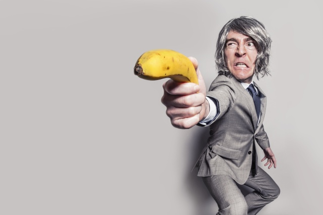 Angry man in a grey suit is pointing a banana at us as it was a gun.