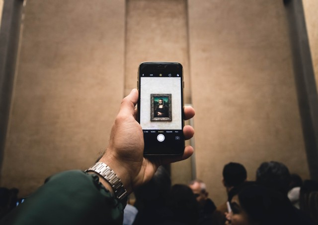 A man's hand wearing a watch holds a smartohone to photograph the Mona Lisa in a crwoded Louvre museum in Paris. We barely see the painting on the small screen.