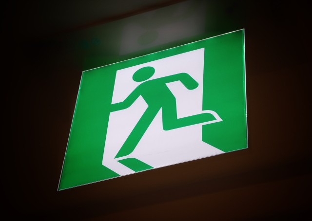 A green emergency exit sign showing a person leaving quickly.