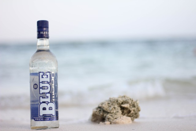 Full Blue Moon vodka bottle on a hazy beach.