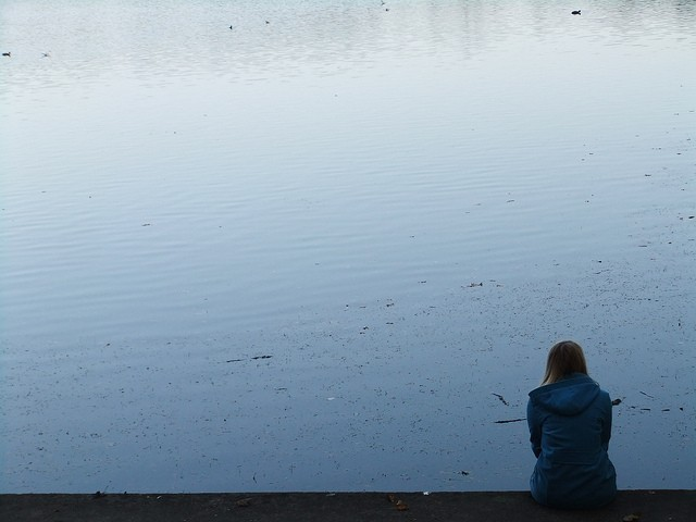 Woman sitting alone and looking at the water
