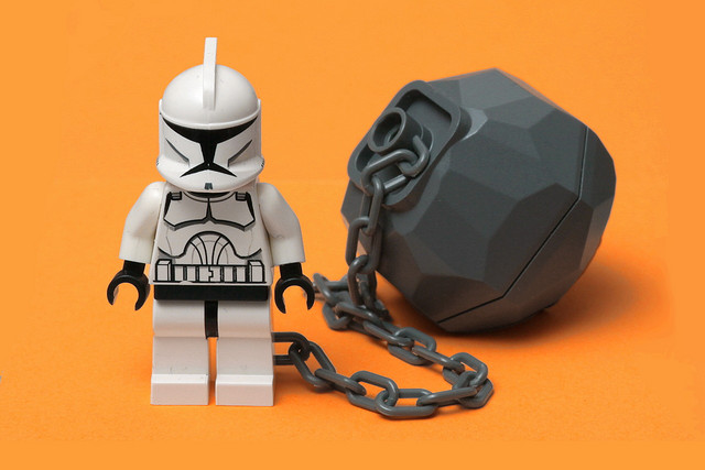 Lego Star Wars. A storm trooper having a huge weight attached to his leg with a chain.