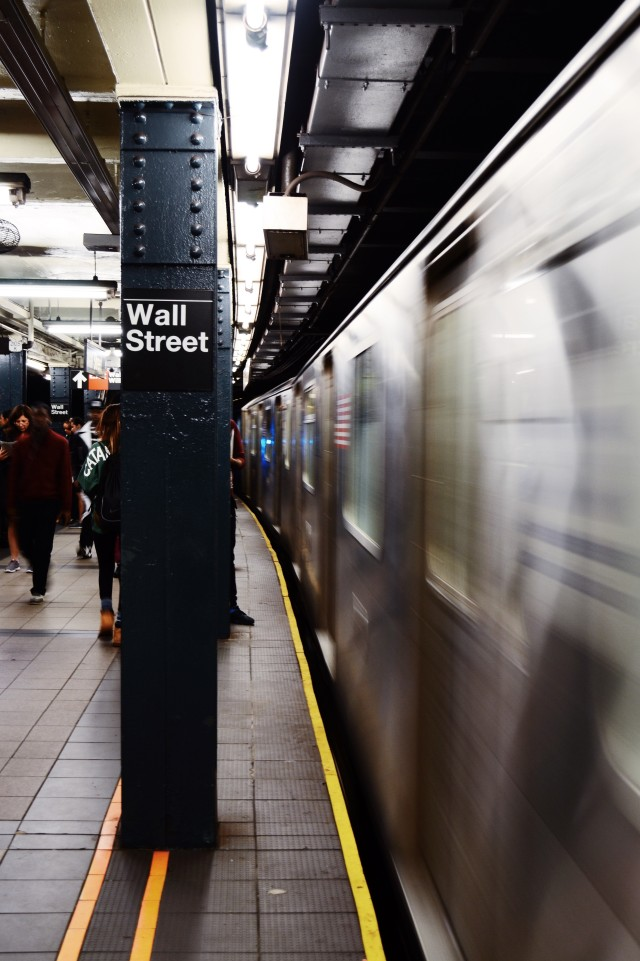 The Wall Street subway station in New York City just as the train starts moving. Some people are walking in the background. There is a lot of movement in that image.