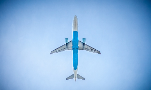 A plane viewed from below flying on a blue sky.