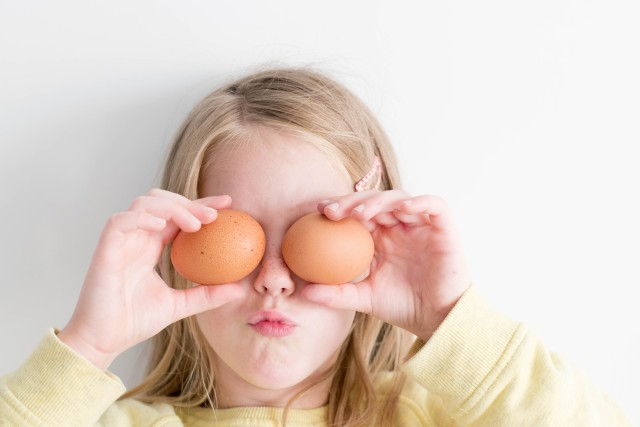 A little girl is playing with eggs, putting them in front of her eyes and making a funny face. It really is!