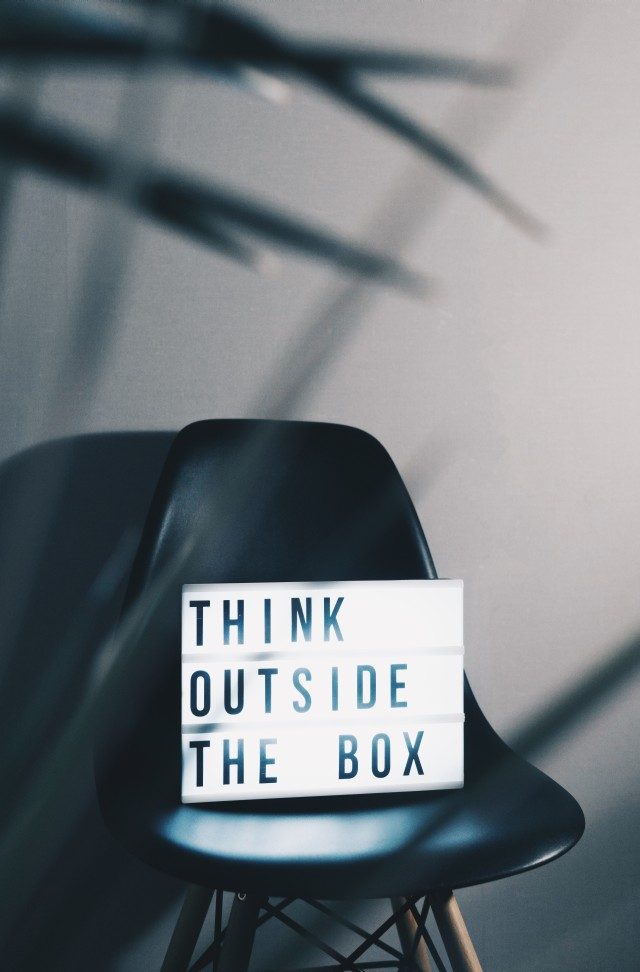 "The famous ""think outside the box"" slogan shown inside a light box sitting on a designer chair. Isn't it ironic?"