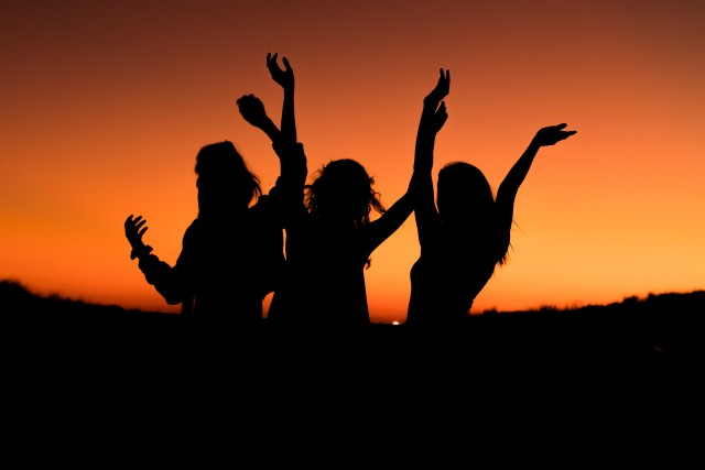 Three women dnacing in the sunset with their hands up.