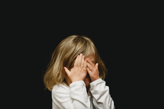 Kid hiding his face with his hands on an all black background