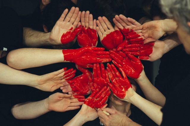 A group of people join their hands. On them a bright red heart is painted with lipstick it seems.