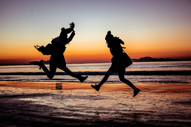 Two people jumping in the evening when the sun sets