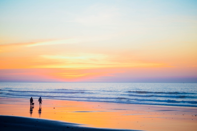 Couple wandering at the beach shortly before sunset. It's a picturesque scene, almost kitsch.