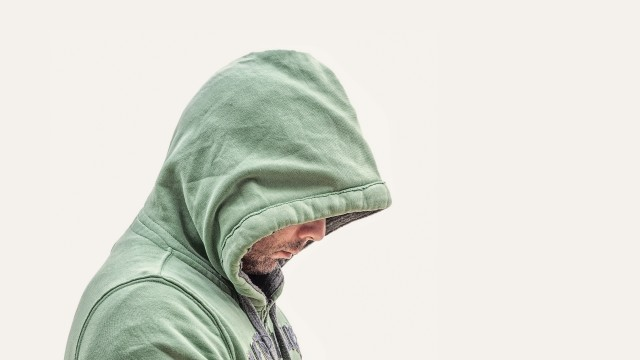 A man in a field jacket hiding below his hood.