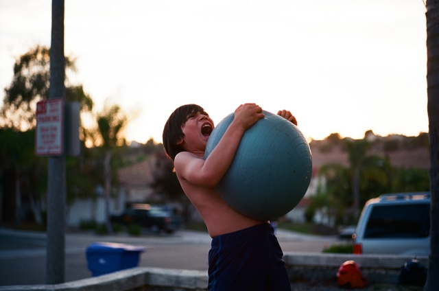 A boy screaming while squeezing a large sitting ball on his naked chest.