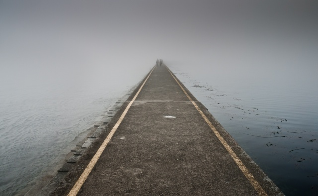 A ded end street leading into the sea on a gray day