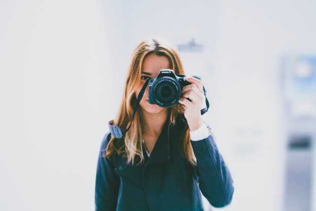 A female photographer looking into the camera with one eye and looking at us with the other.
