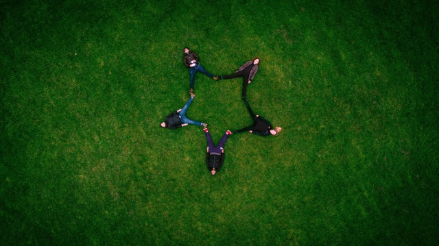 5 friends lying on the grass and forming a star with their bodies