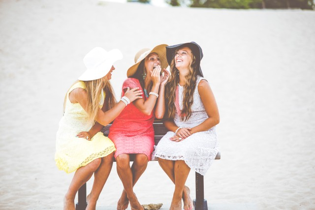 three young ladies wearing stylish hats chat on a bench at the beach