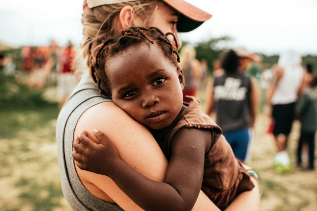 A white woman holding a black toddler in Haiti. There are peopel in the background. The baby needed a hug it seems.