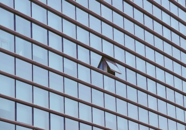 An open window in a highrise office building, all others are closed.