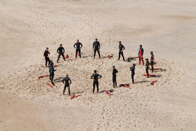 A team of rescue swimmers congregates at the beach in a circle. There are 3 women and 10 men. They all have almost black wet suits on.