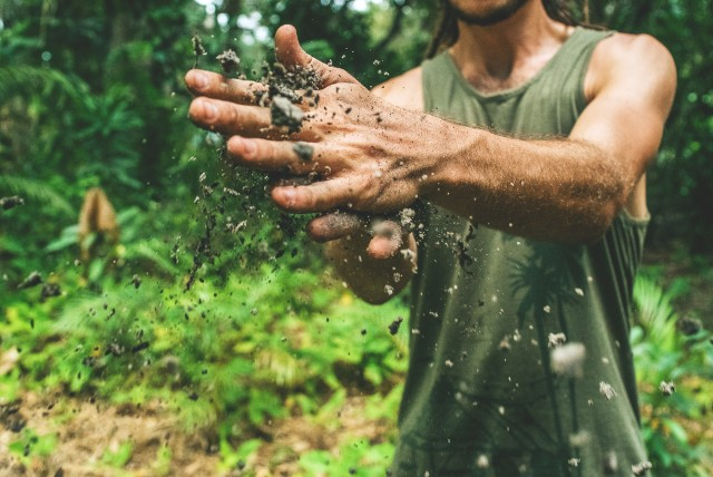 Man standing in the jungle wearing a khaki muscle shirt and cleaning his hands from the mud. We don't see his face, just the body until the chin.