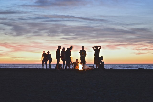 Campfire with a group of young adults around it on the San Franciso beach in the evening, the sun is almost set.