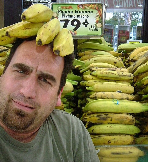 Man wearing a bananas on his head and looking funny.