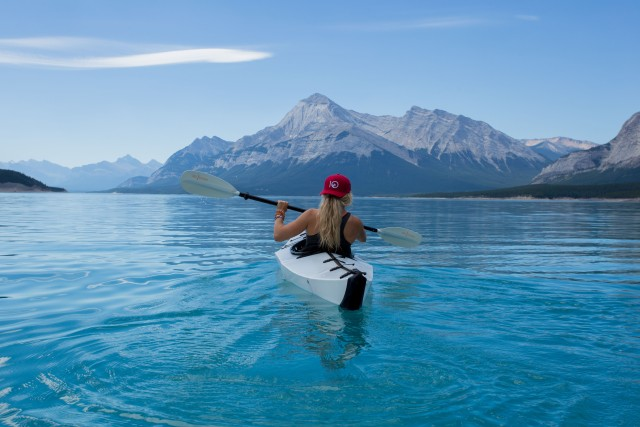 Kayaking in the Canadian mountains. A young woman in beautiful sunny weather.