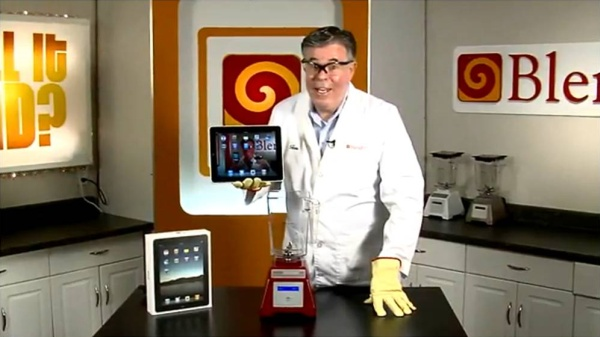 Screenshot from the Will it Blend video series. A man dressed in white - like in a lab - wearing protective glasses stands in front of the blender and talks.