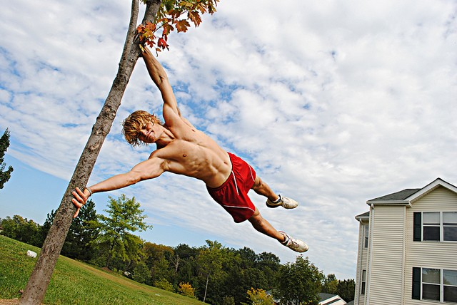 A guy is preforming a parkour move called the flag on a pole - he hangs horizontally from that pole as if he was a flag
