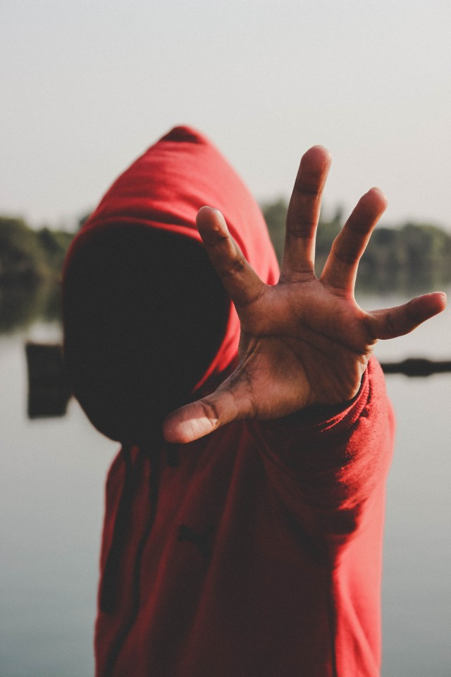 A man wearing a red hoody sweat-shirt stretching his hand forward with his palm open. He looks scary because you can't see his face and the hand seems to want to grab you.