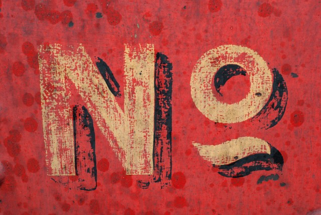 """No"" written somewhere on an alreyd pretty dated surface with a red background."