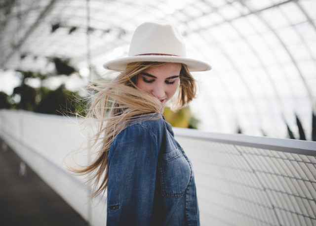 Cute blonde girl wearing a large white hat. It's windy it seems. It seems she stands on a bridge. It fades in the background though. Very picturesque.