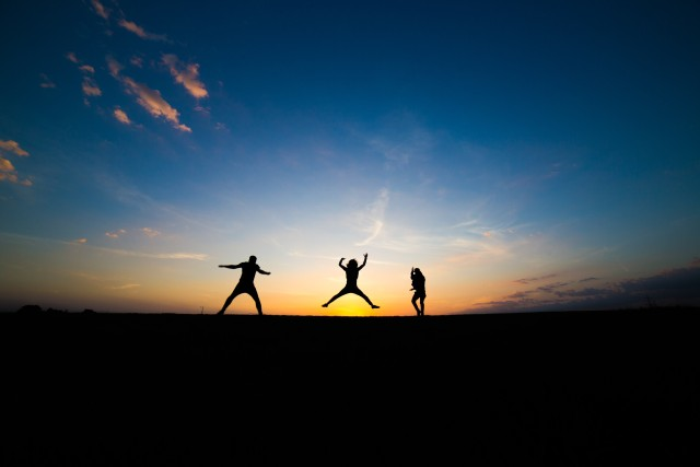 "Three people happily jumping over a sunset. One already landed, the one in the middle is just above the sun, the third on seems to hold a backpack. We only see the silhouettes. It's an inspiring image called ""happiness""."