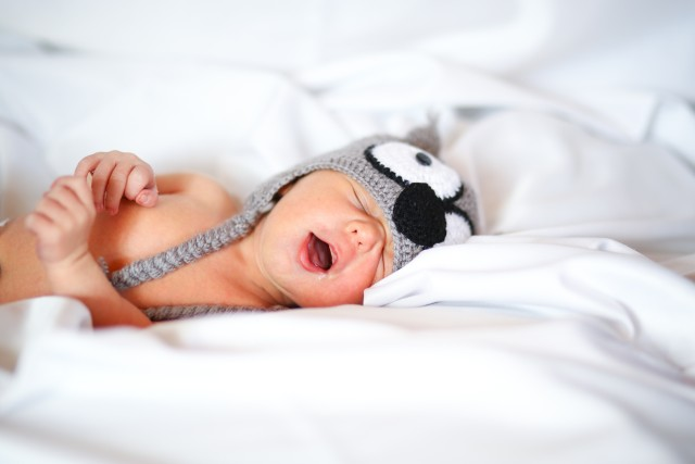 Cute sleeping baby with open mouth wearing a grey owl hat and lying in a bed with all white sheets.