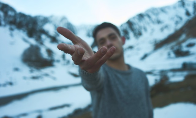 Young man reaches out to person behind camera. Behind him snow covered mountains loom large.